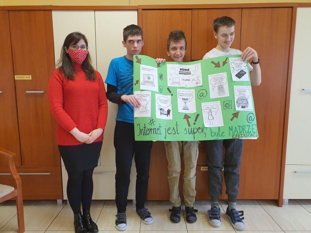 z lewej stoi pani w czerwonej bluzce obok trzech chłopców trzyma zielony plakat