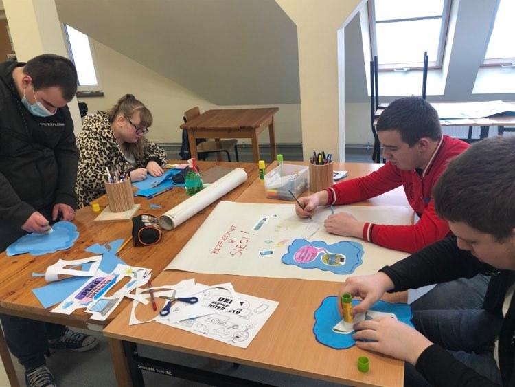 czworo uczniów wykleja obrazki i wycina ilustracje