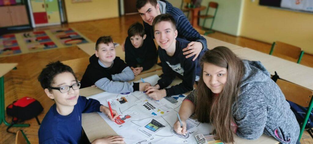 grupa dzieci pięciu chłopców i jedna dziewczynka pochylają się nad kartka i uśmiechają
