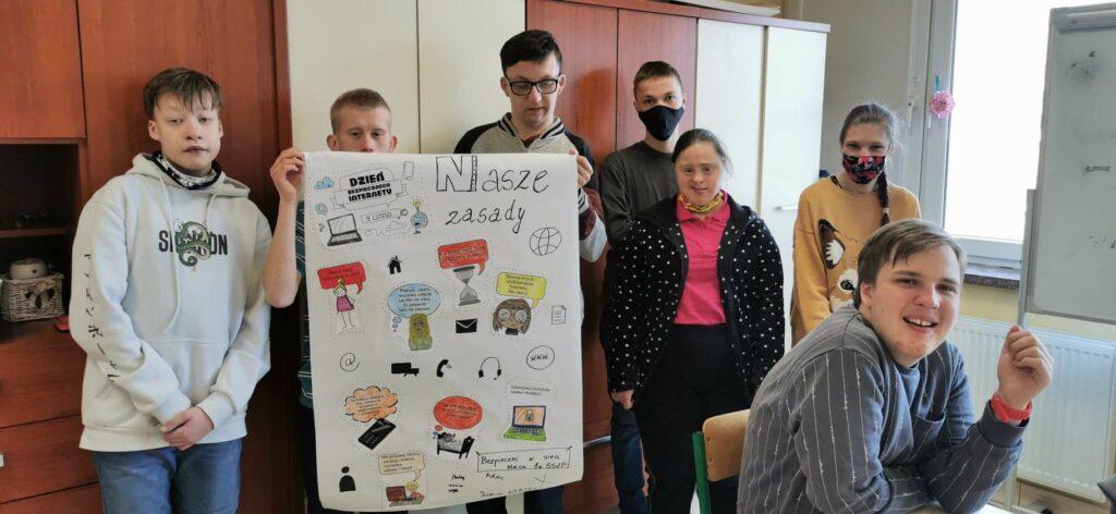 chłopcy trzymają białą kartkę plakat, obok stoją dwie dziewczynki, na pierwszym planie siedzi uśmiechnięty chłopiec.