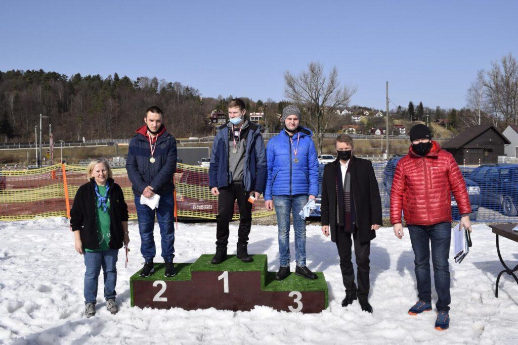 na podium stoją chłopcy z medalami, obok pan starosta i organizatorzy olimpiady