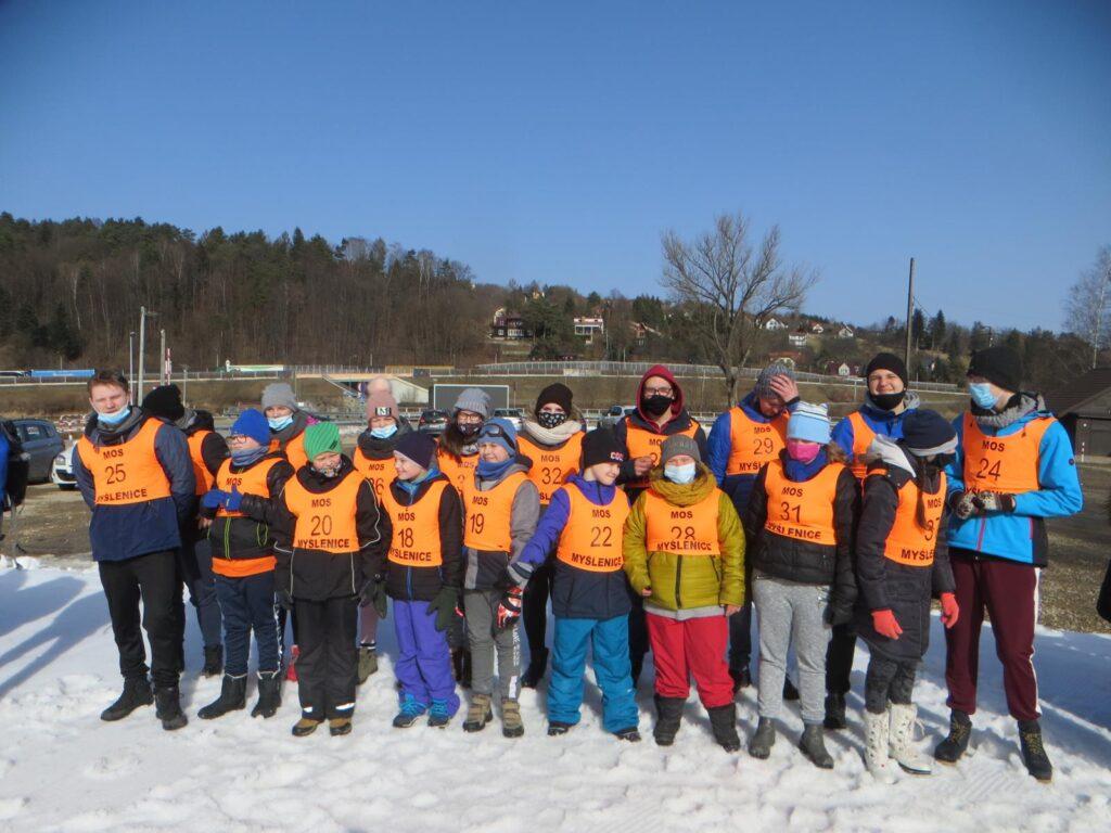 grupa uczniów w zimowych ubraniach i pomarańczowych kamizelkach stoją w szeregu