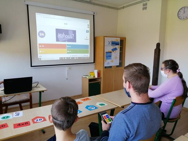 Sala lekcyjna. W ławkach siedzą uczniowie. Dwóch chłopców i jedna dziewczyna. Przed nimi biała ściana, na której wisi ekran z wyswietlanymi działaniami matematycznymi. Po lewej stronie ławka z laptopem. W rogu sali szafa.