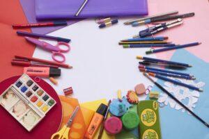 na kolorowych kartkach leżą przybory szkolne (nożyczki, farby, ołówki )