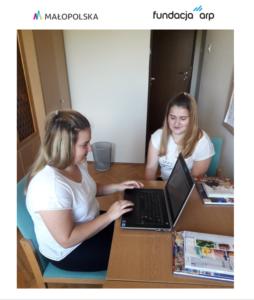 dwie dziewczynki siedzą przy ławce i patrzą na laptopa
