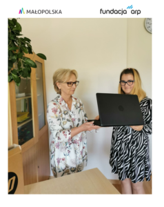 Pani Dyrektor wręcza czarnego laptopa dziewczynie